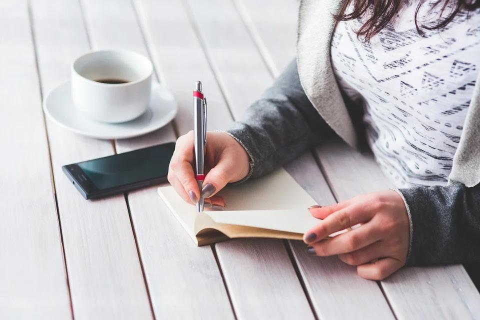 moça fazendo anotações imagem ilustrativa passos para abrir uma franquia