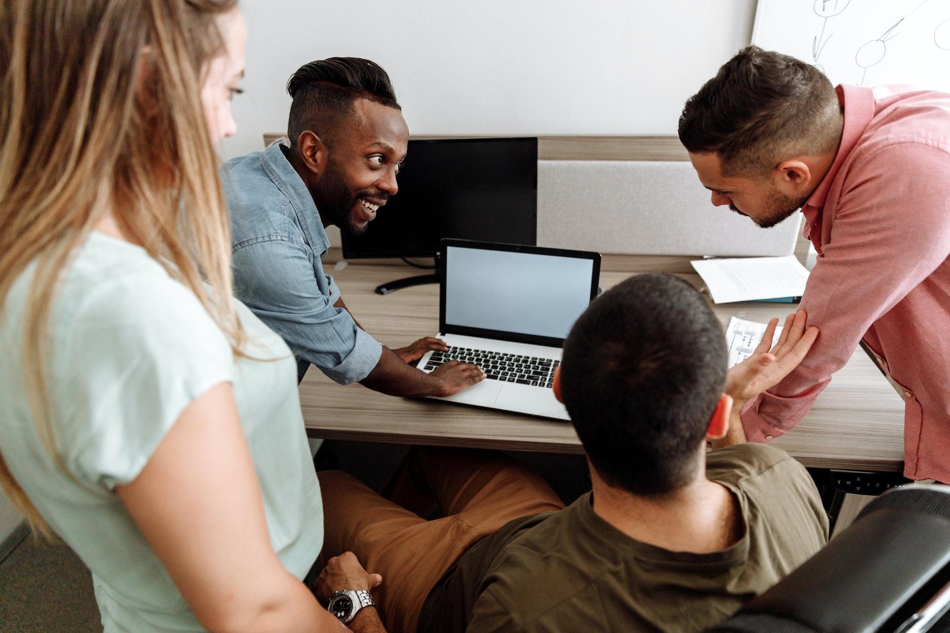 Imagem de quatro pessoas olhando para um computador em uma mesa de escritório. Imagem ilustrativa texto pequenas ideias grandes negócios.