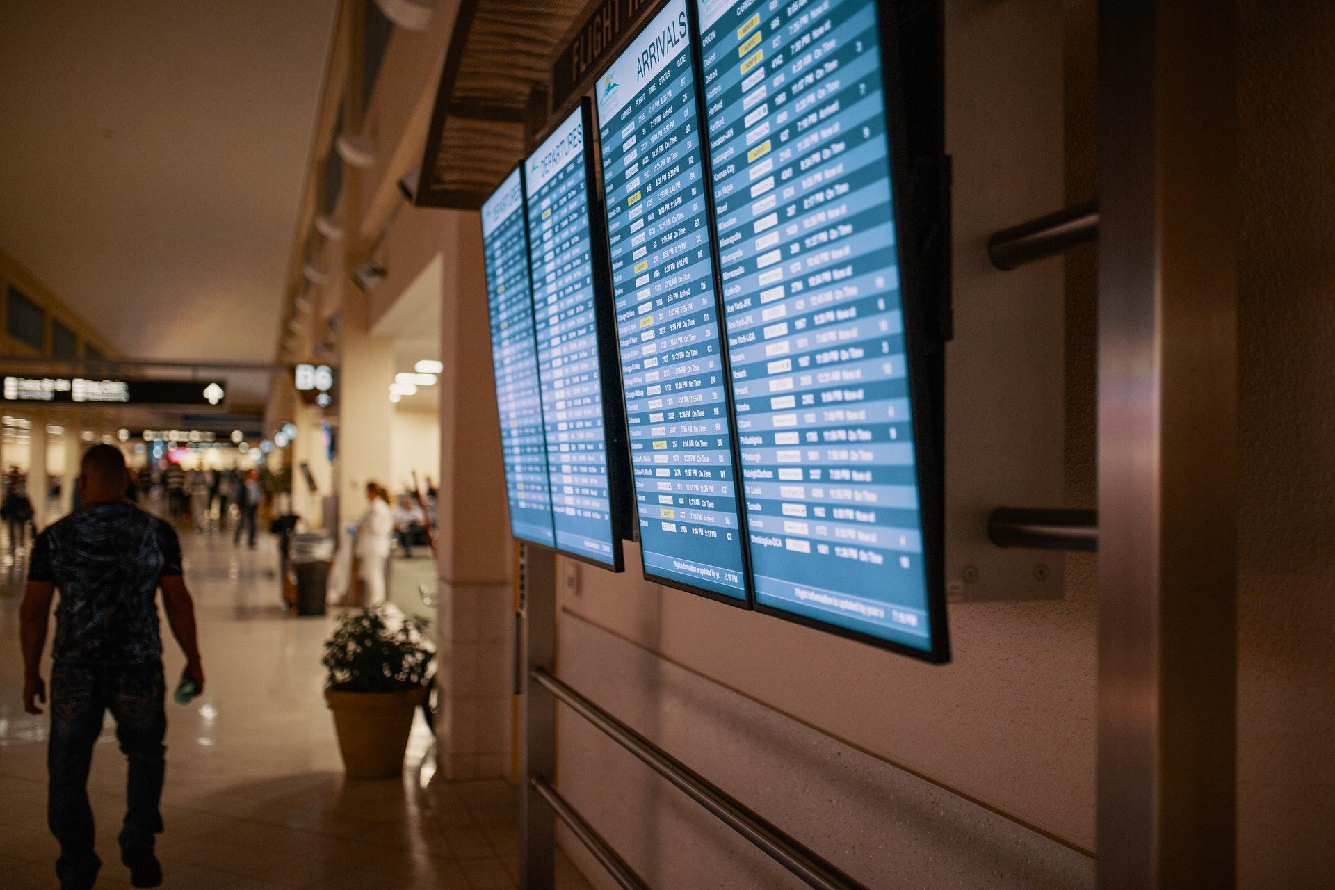 Vemos um telão de aeroporto com os horários de voos (imagem ilustrativa). Texto: tendências de franquias para investir.