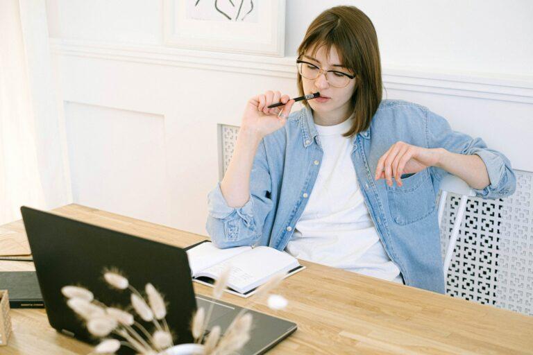 Imagem de uma mulher olhando para o computador de forma pensativa. Imagem ilustrativa texto tendências de franquias para investir.