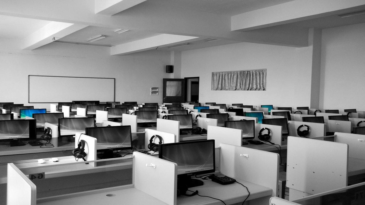 Vemos uma grande sala com várias mesas e computadores (imagem ilustrativa). Texto: tendências de negócios.