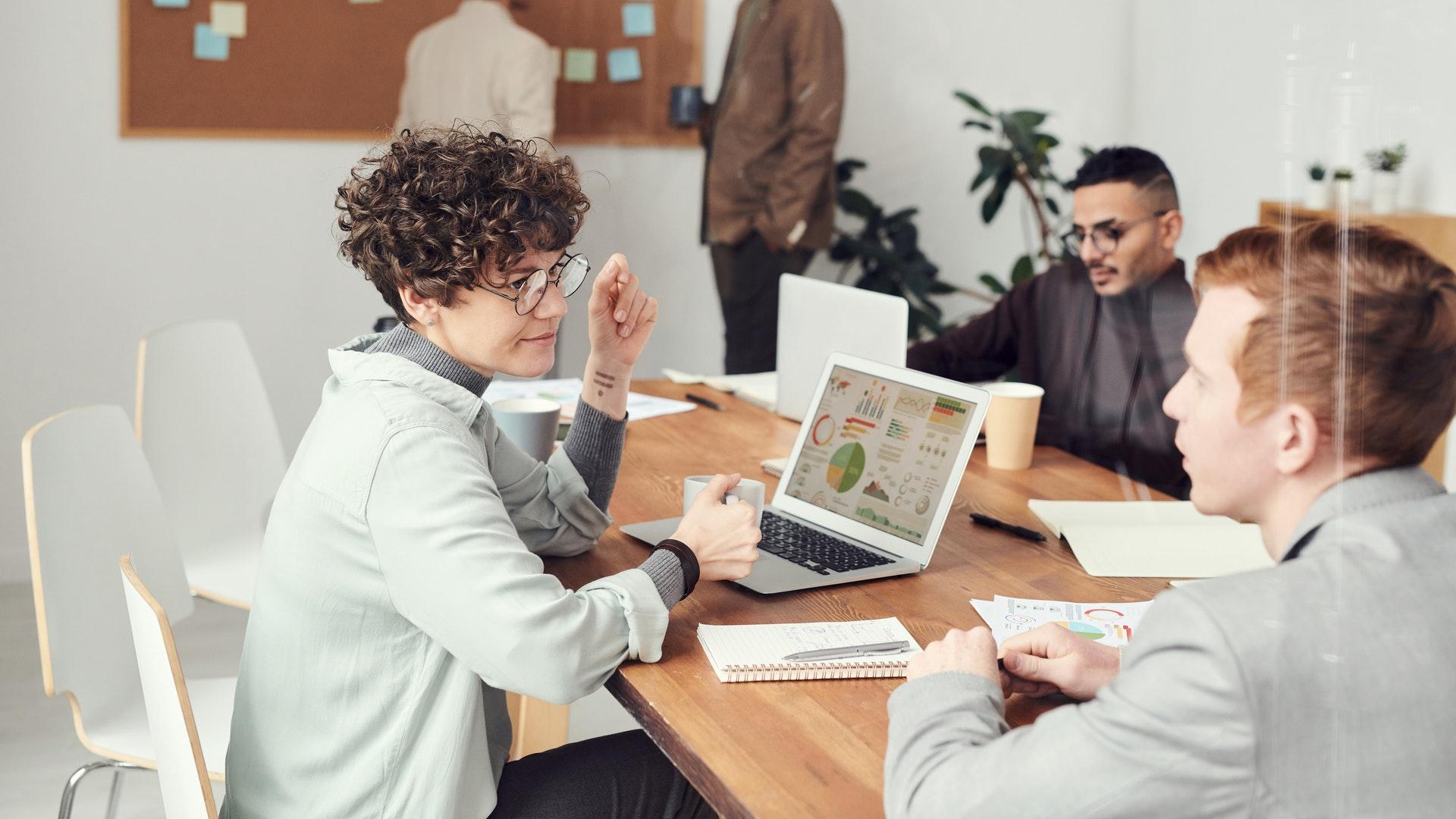 Imagem de uma mesa cheia de pessoas em um escritório. Imagem ilustrativa texto tendências de negócios.