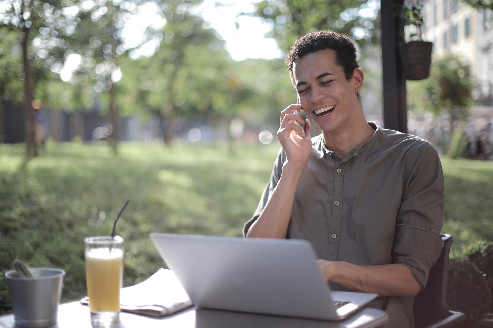 Vemos um homem sorrindo enquanto trabalha em uma área externa; sobre uma mesa vemos computador, jornal e um copo de suco (imagem ilustrativa). Texto: tipos de franquia baratas.