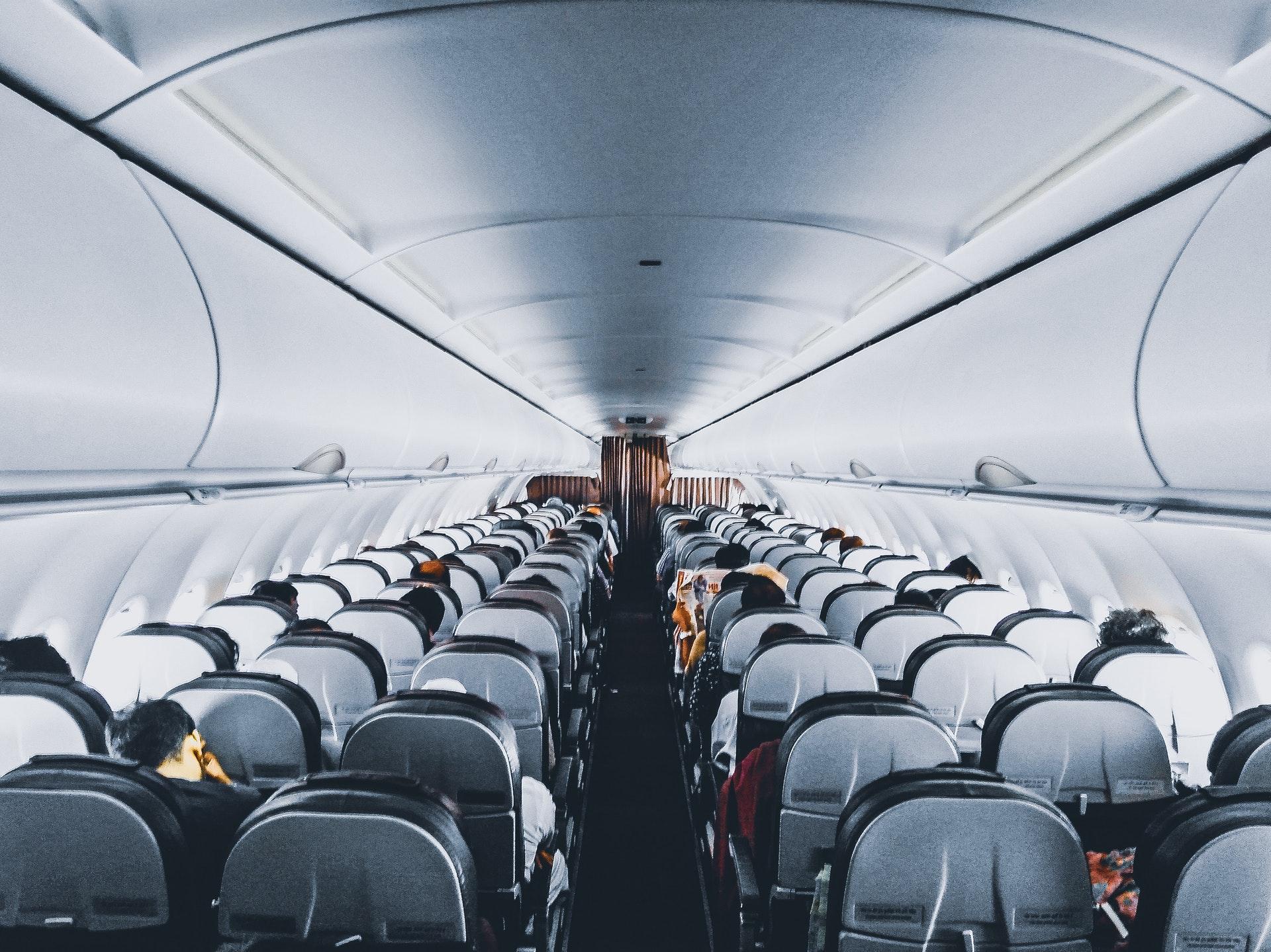 Vemos o corredor de um avião e várias poltronas vazias (imagem ilustrativa). Texto: tipos de franquia baratas.