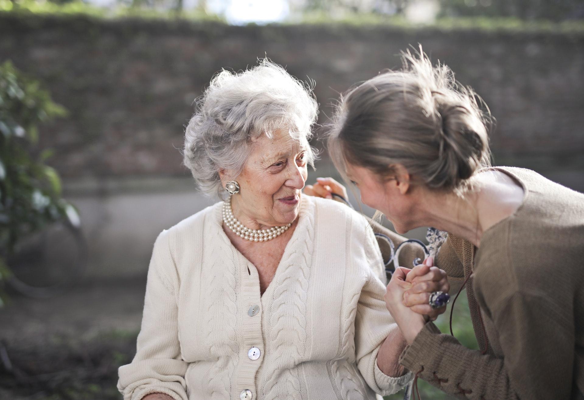 Vemos uma mulher jovem conversando com uma idosa (imagem ilustrativa).