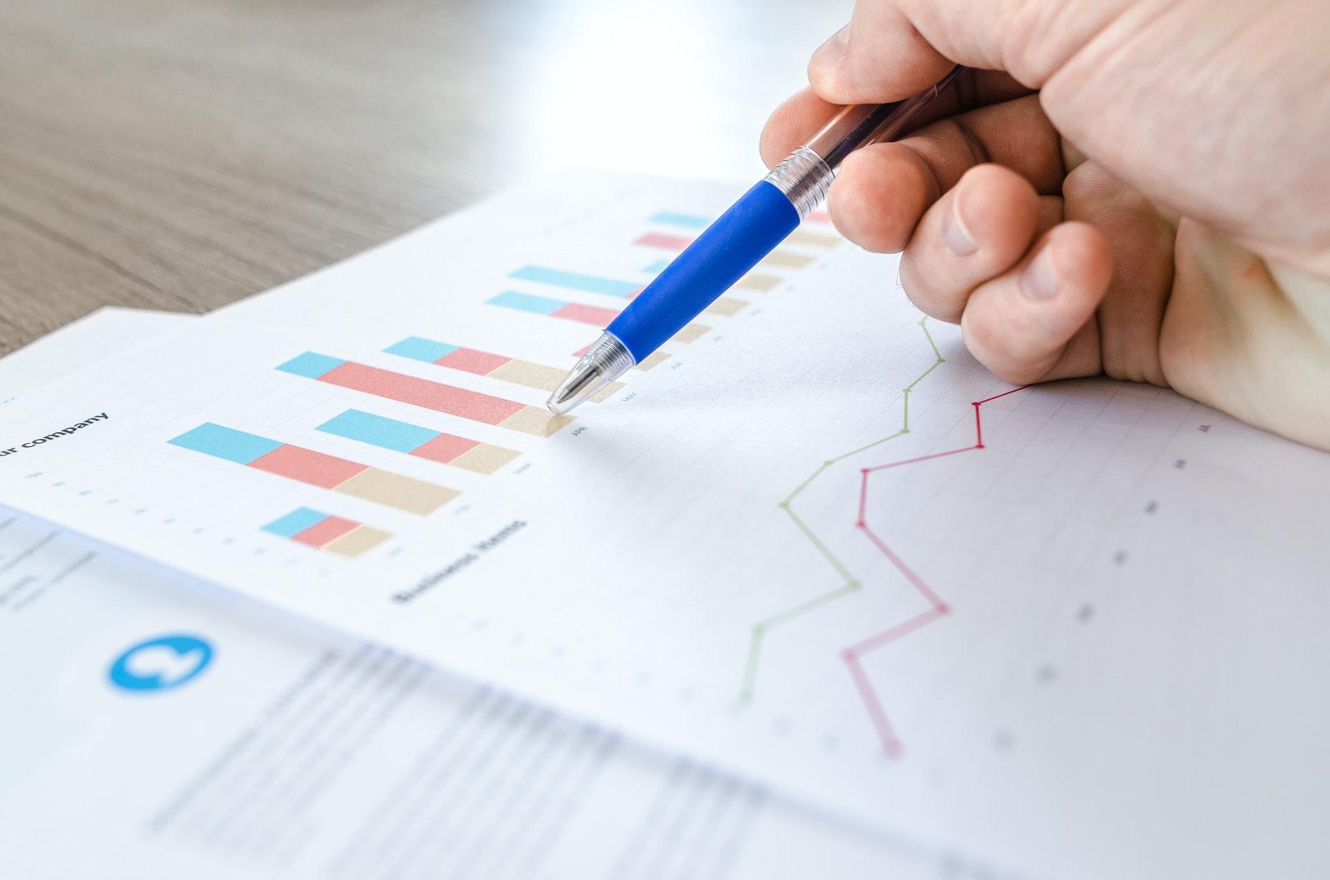 Vemos que uma pessoa tem sobre a mesa alguns gráficos impressos; com uma caneta, ela os analisa (imagem ilustrativa). Texto: vantagens de ter uma franquia.