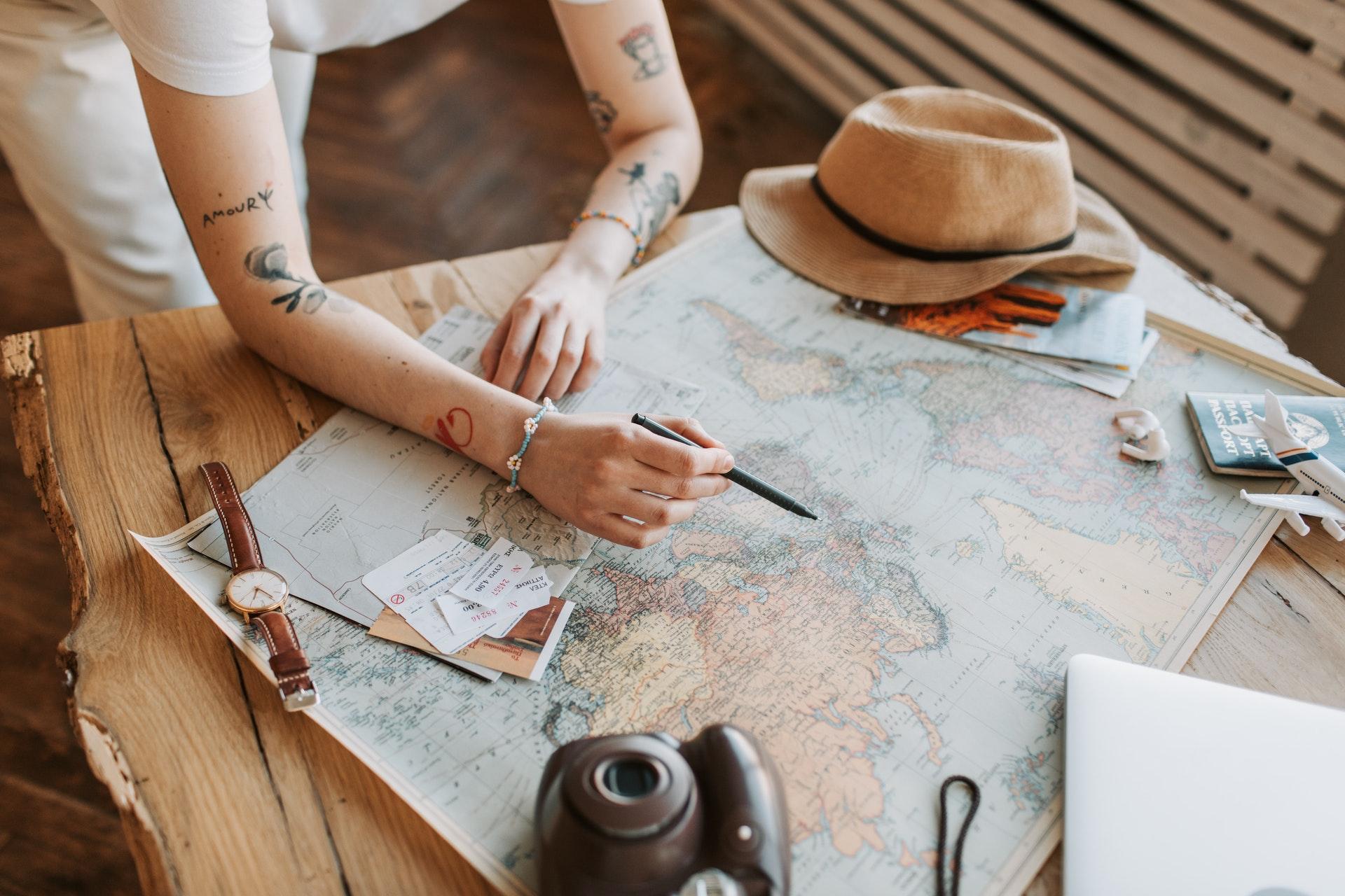 Vemos uma pessoa apontando para um lugar em um mapa-múndi. Ao redor vemos chapéu, relógio, câmera fotográfica, passaporte e outros acessórios (imagem ilustrativa).