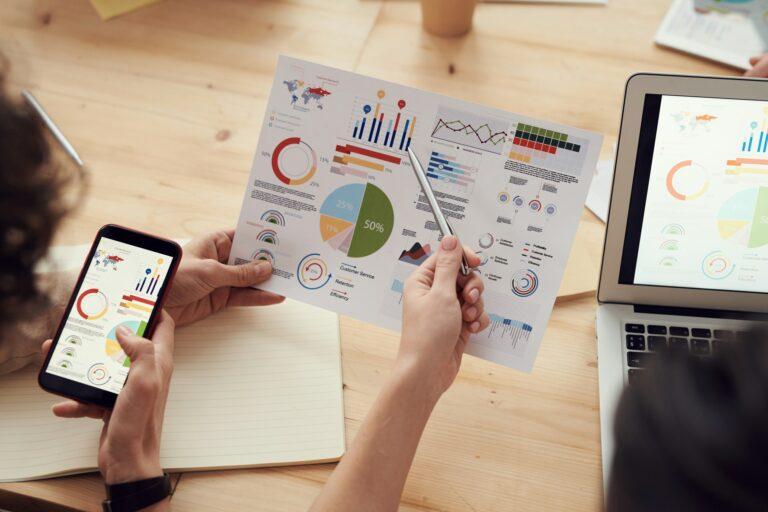 Imagem de uma folha com gráficos e uma pessoa analisando os dados. Imagem ilustrativa texto vantagens de ter uma franquia.