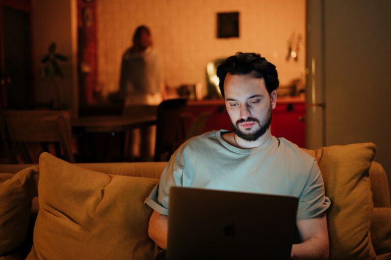 Imagem de um homem olhando um computador sentado em um sofá. Imagem ilustrativa texto como ganhar dinheiro em casa.