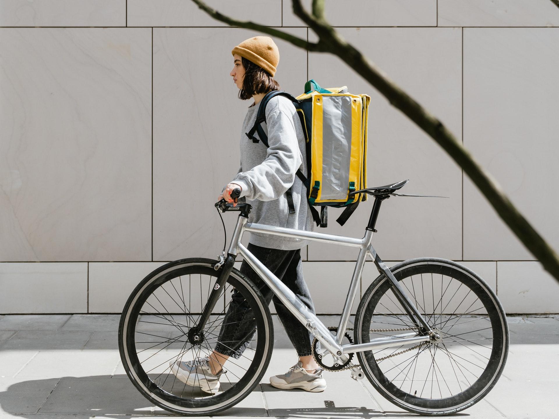Imagem de um entregador com uma bolsa nas costas ao lado de uma bicicleta. Imagem ilustrativa texto empreender no pós pandemia.