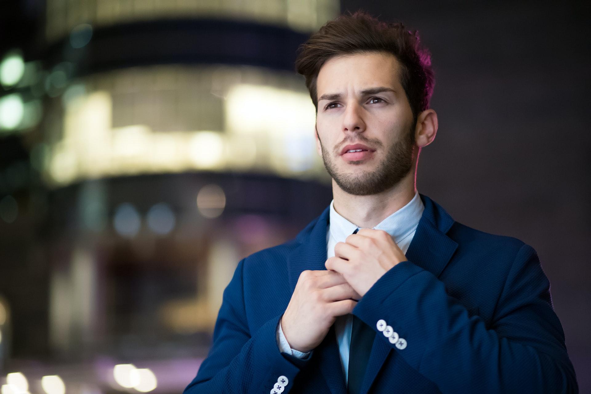 Imagem de um empresário ajustando a gravata. Imagem ilustrativa texto empreender no pós-pandemia.