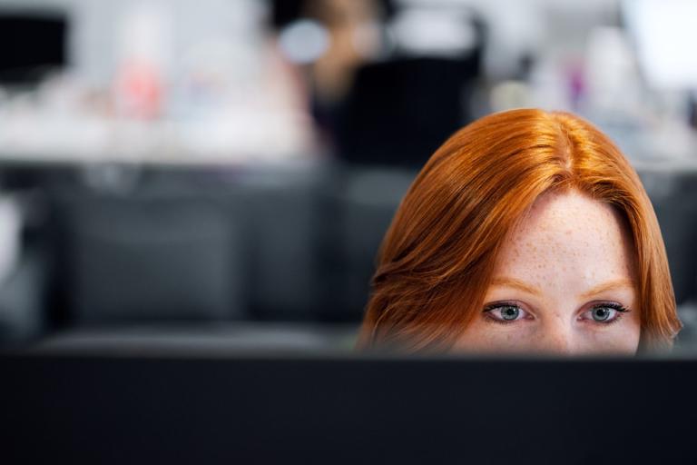moça ruiva em frente a tela de computador imagem ilustrativa empresa home office