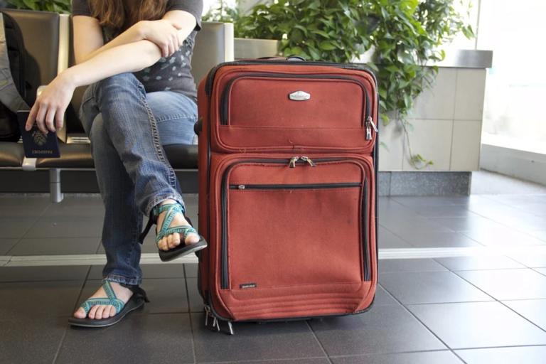 moça sentada ao lado da sua mala de viagem ilustrativo encontre sua viagem tudo sobre