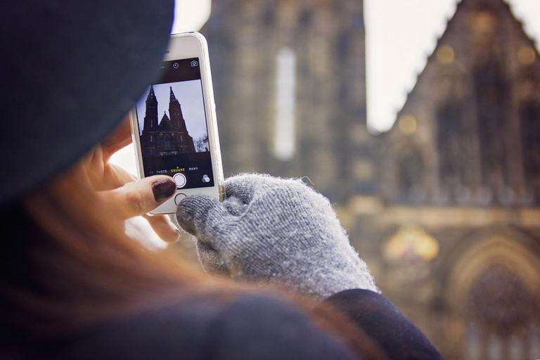 moça tirando foto com o celular de ponto turístico ilustrativo franquia de turismo é boa investir