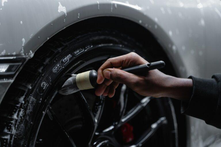 Imagem de uma pessoa limpando a roda de um carro. Imagem ilustrativa texto franquias baratas automotivas 2022.