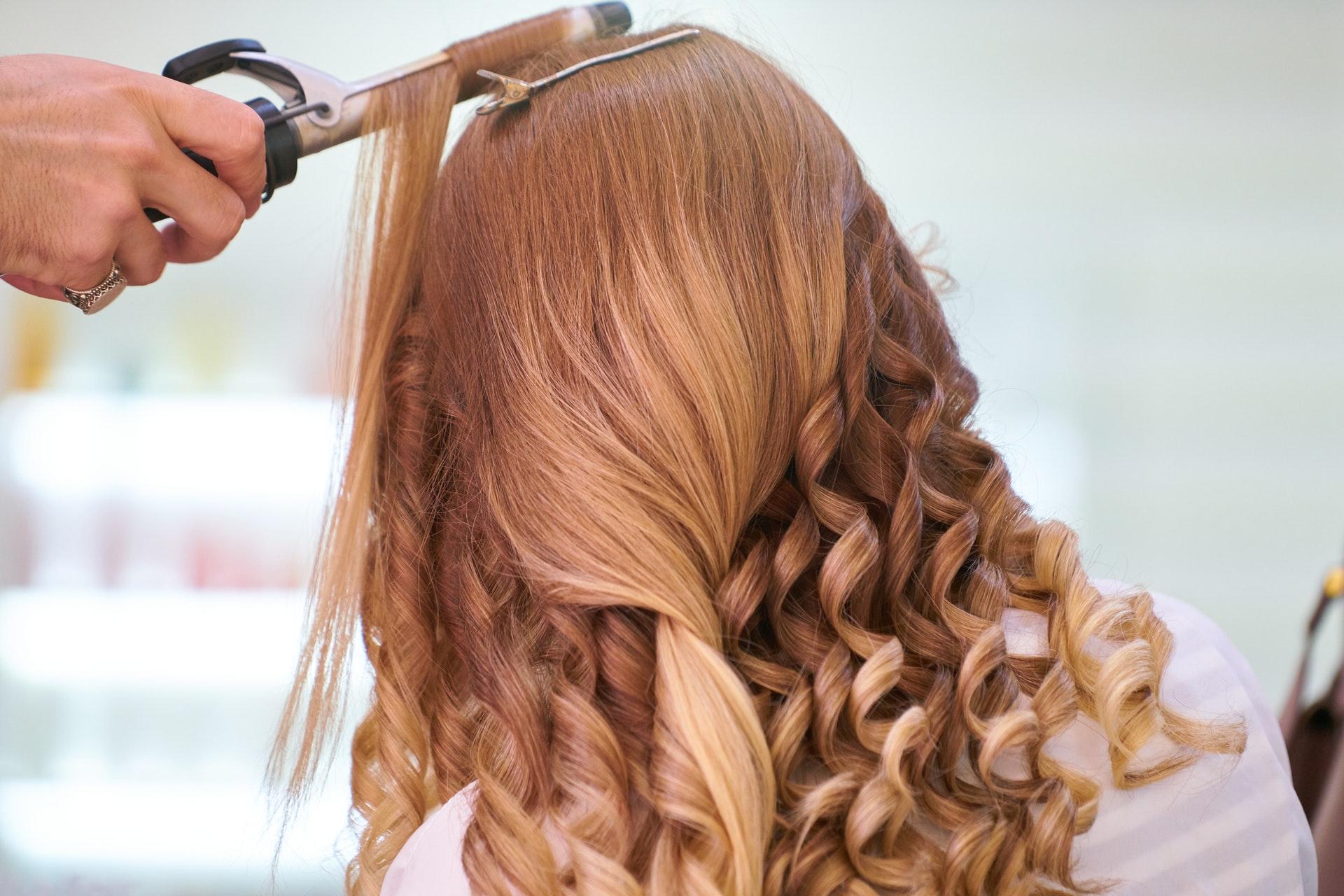 Imagem de uma mulher fazendo cachos no cabelo. Imagem ilustrativa texto franquias baratas beleza 2022.