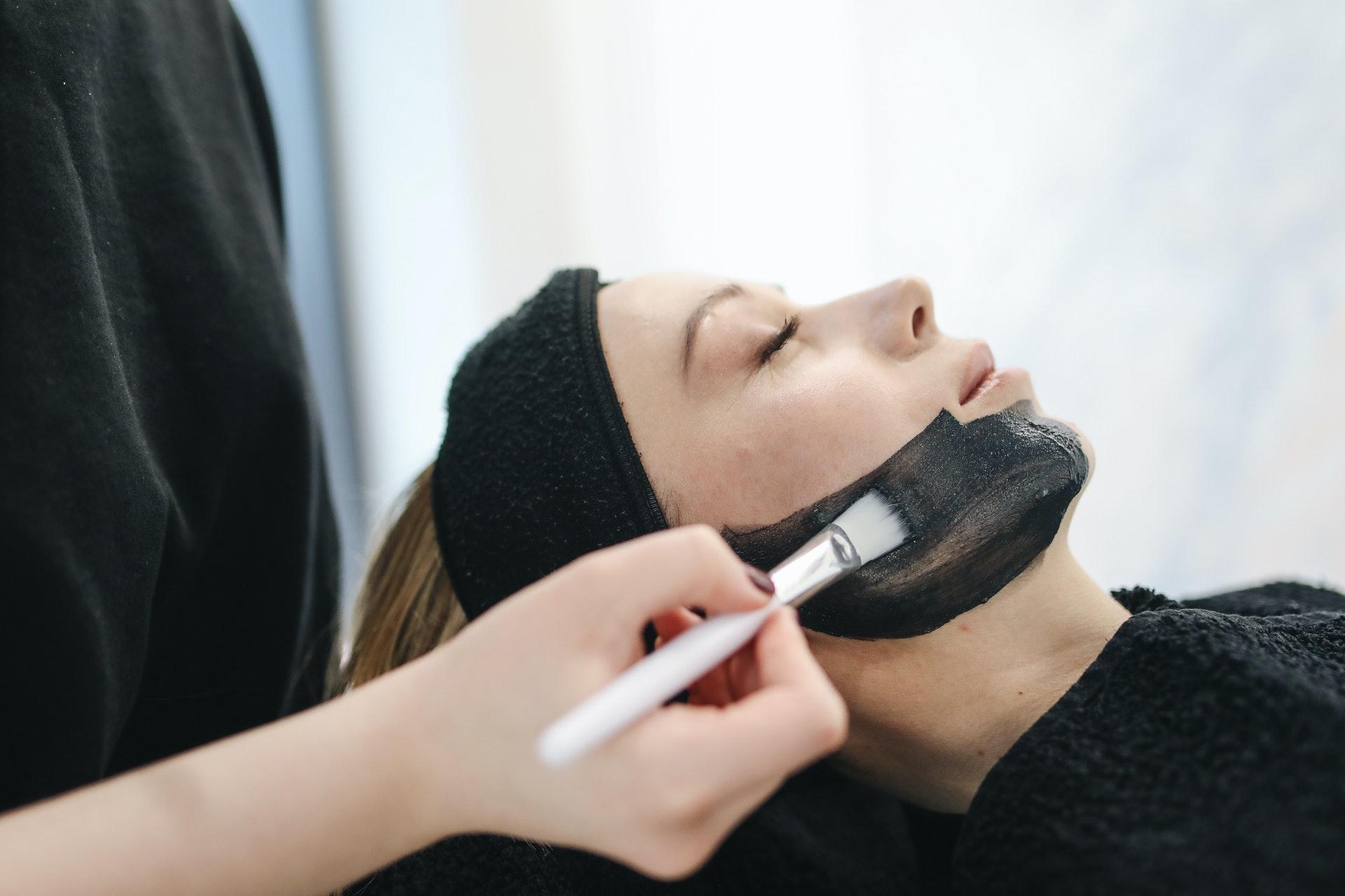 Imagem de uma mulher passando um produto negro no rosto para tratamento. Imagem ilustrativa texto franquias baratas beleza 2022.