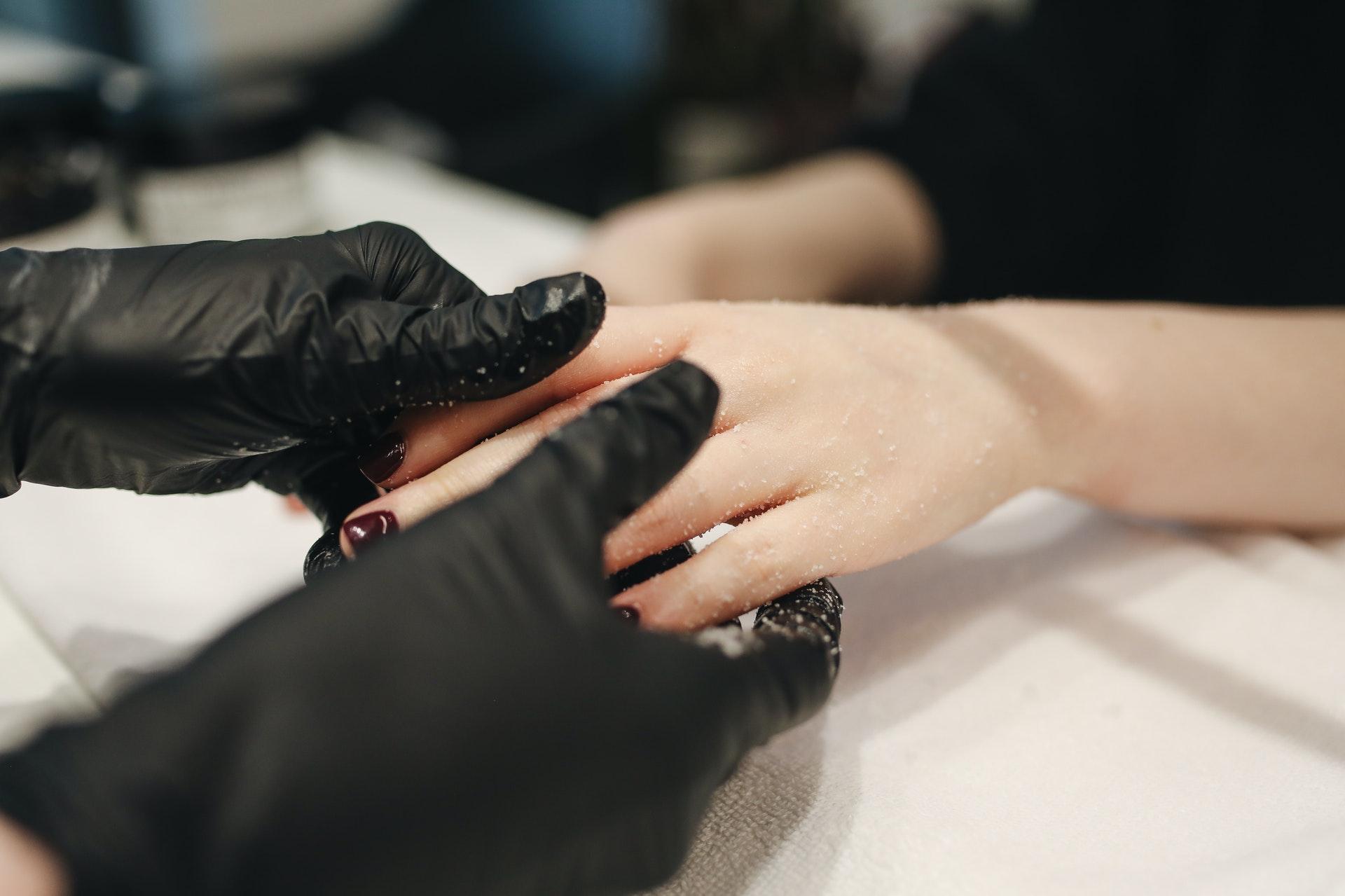 Imagem de uma mão fazendo massagem em outra mão. Imagem ilustrativa texto franquias baratas beleza 2022.