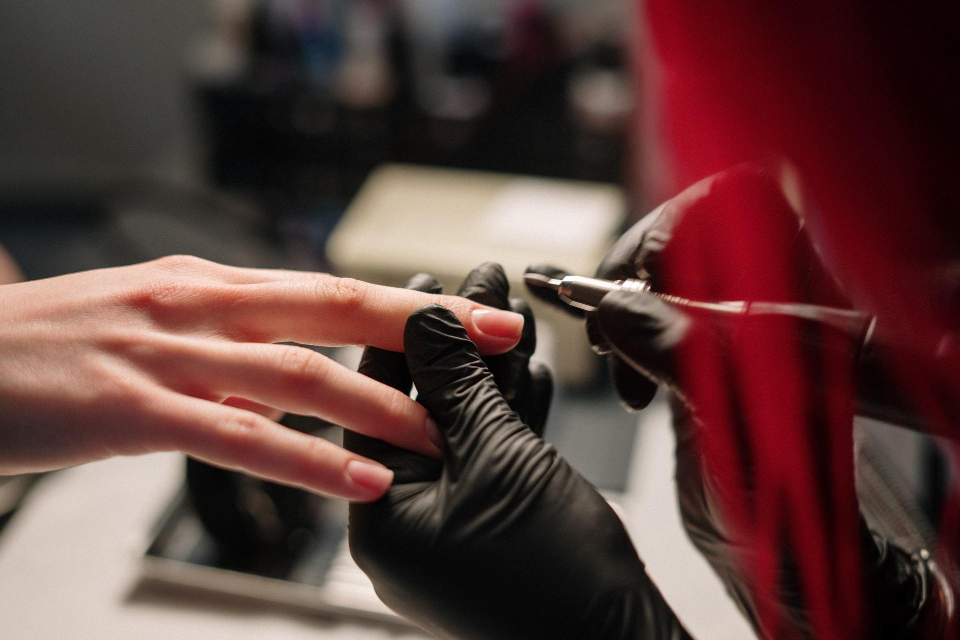 Imagem de uma mão fazendo as unhas de uma outra mão. Imagem ilustrativa texto franquias baratas beleza 2022.