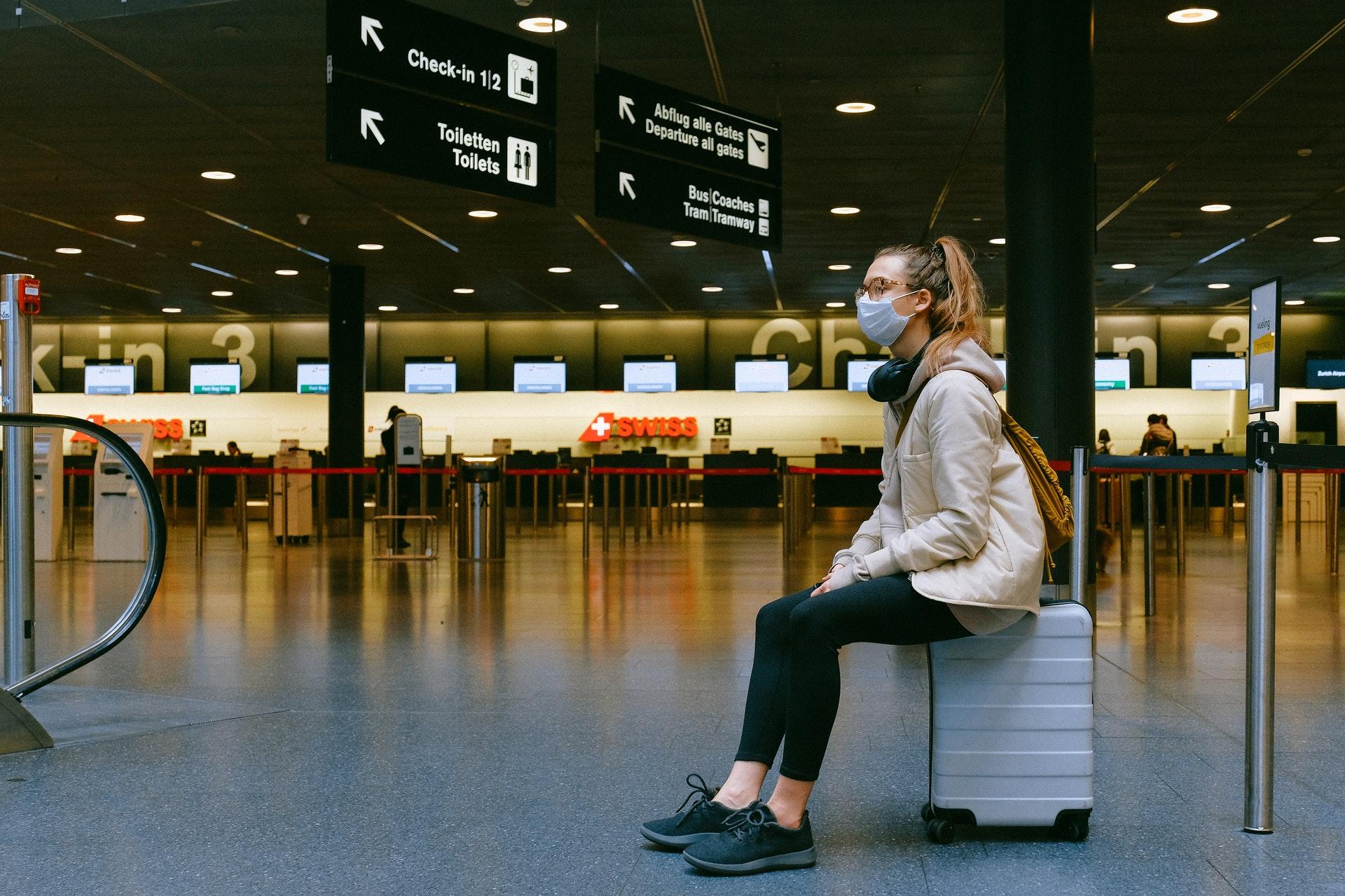 Imagem de uma mulher sentada em uma mala no saguão de um aeroporto usando máscara. Imagem ilustrativa texto franquias boas e baratas 2022.