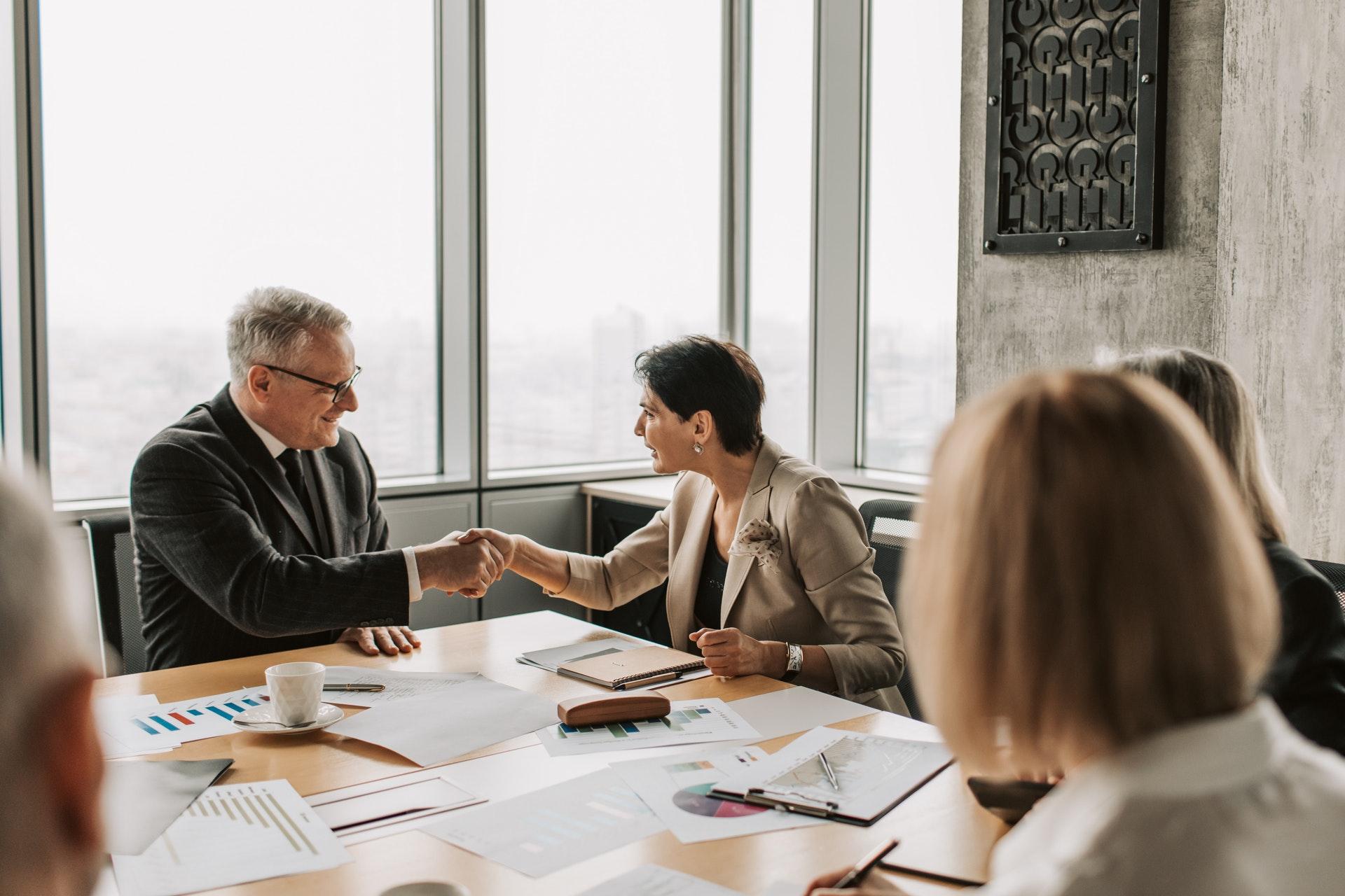 Imagem de duas pessoas fechando negócio em uma mesa de reuniões se cumprimentando. Imagem ilustrativa texto franquias boas e baratas 2022.