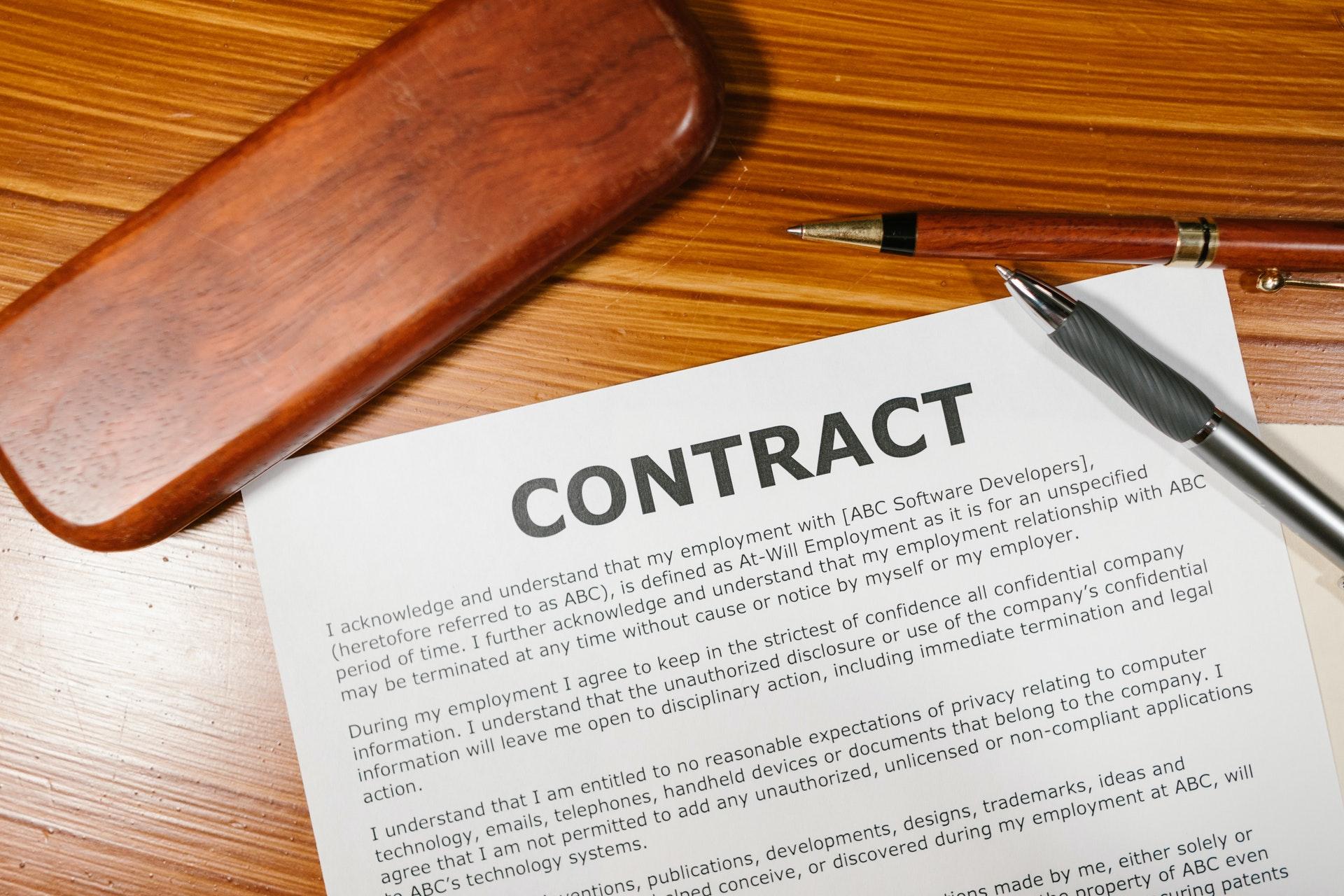 Imagem de um contrato e uma cena em cima dele. Imagem ilustrativa texto licenciamento e fraquia.
