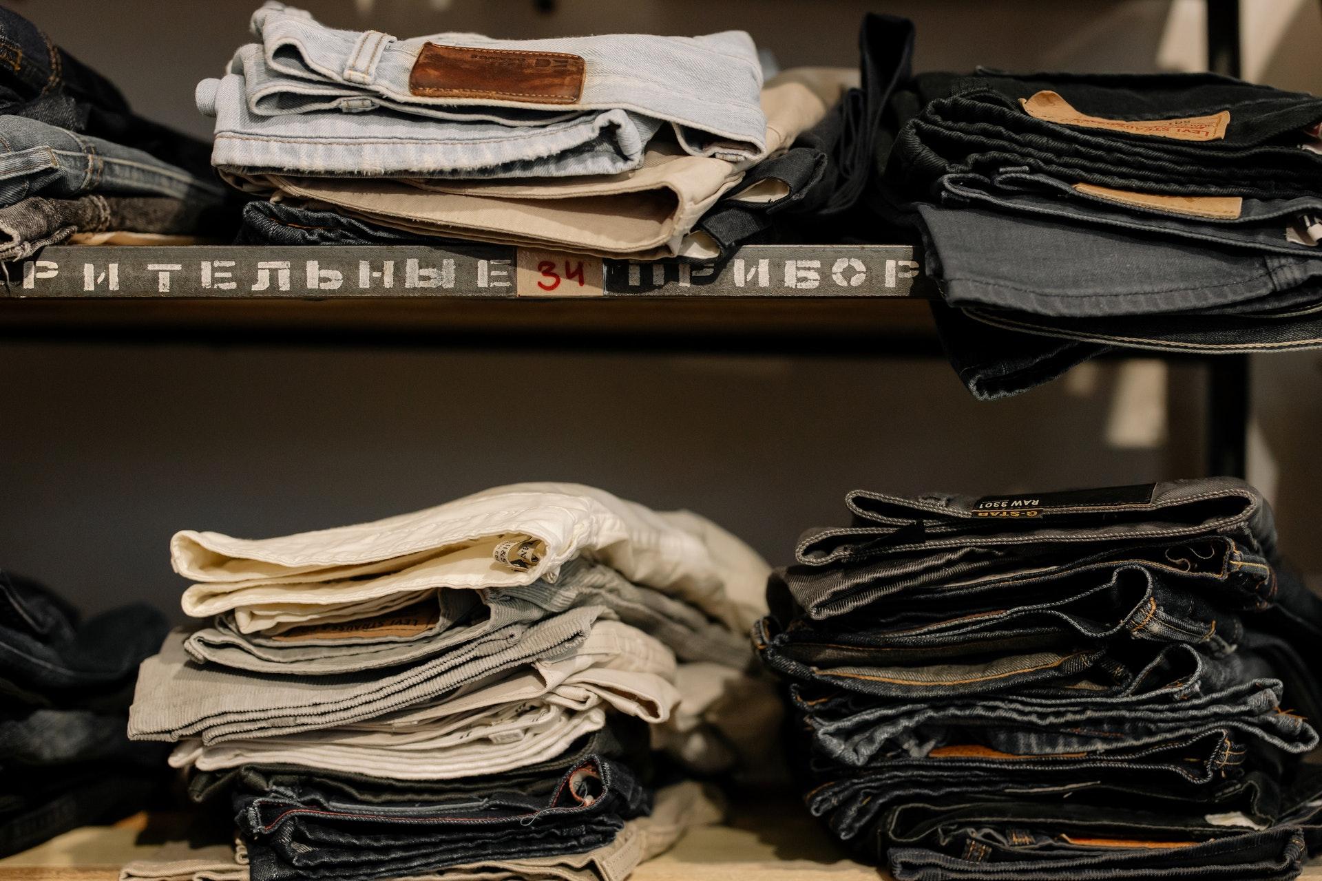 Imagem de calças dobradas e empilhadas em uma prateleira.
