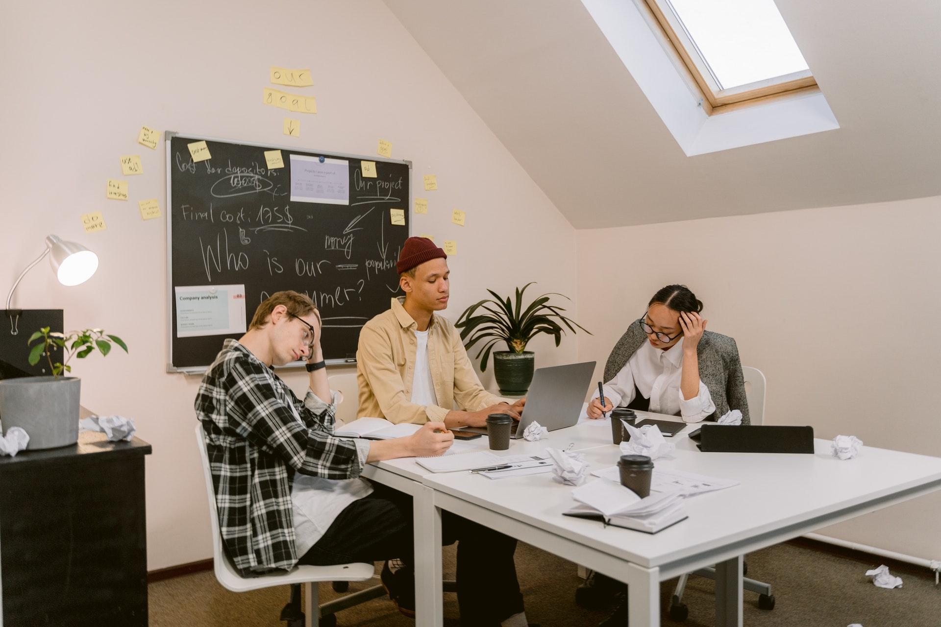 Imagem de três pessoas em reunião sentados ao redor de uma mesa. Imagem ilustrativa texto mvp de franquia.