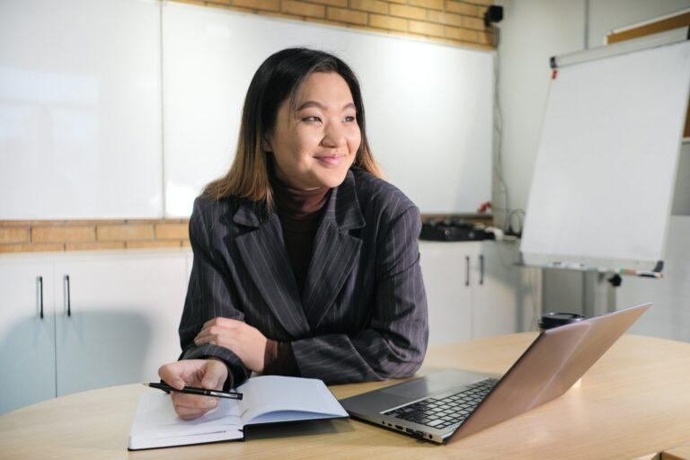 Imagem de uma mulher sorrindo sentada em uma mesa em frente um computador. Imagem ilustrativa texto pequenos empreendimentos lucrativos.