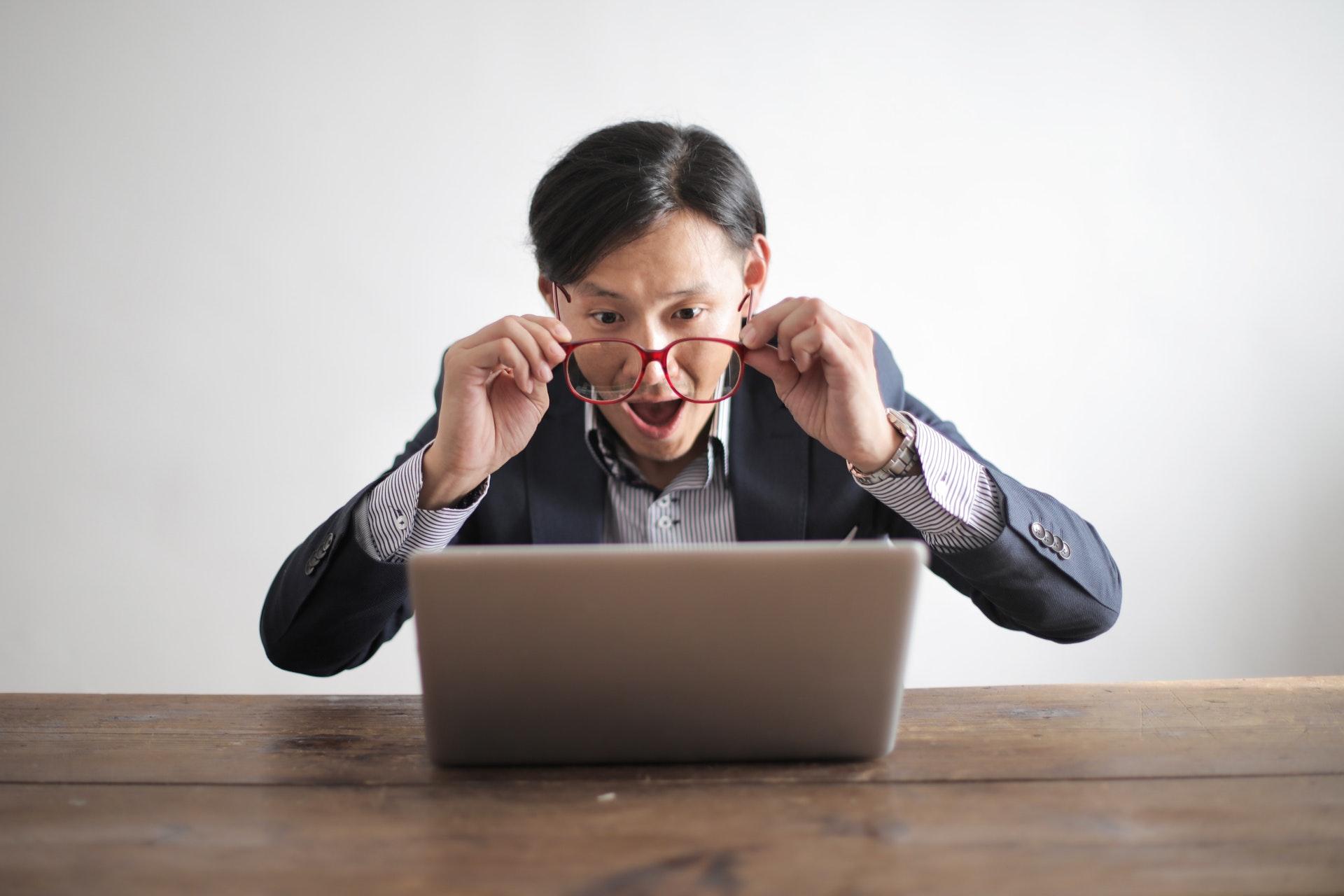Imagem de um empreendedor olhando para o computador e fazendo cara de surpresa. Imagem ilustrativa texto perfil do franqueado.