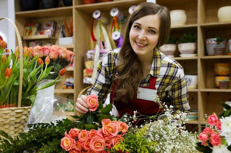 mulher sorrindo cuidando da sua floricultura imagem ilustrativa ter sucesso empreender